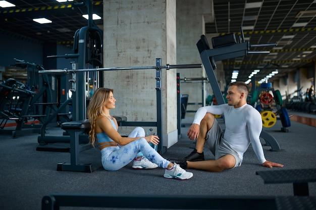 부부는 체육관에서 피트니스 훈련 후 바닥에서 휴식