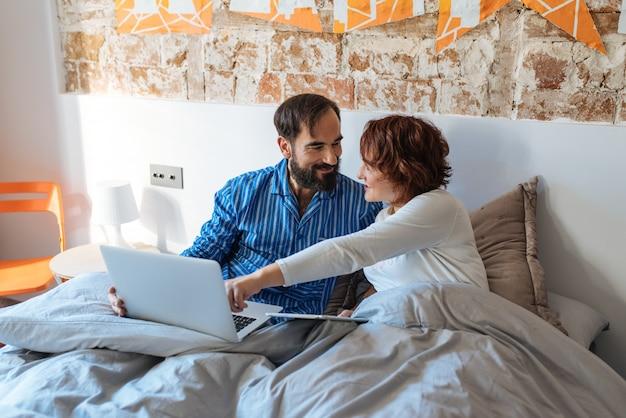 コンピューターとタブレットのベッドで自宅でリラックスしたカップル