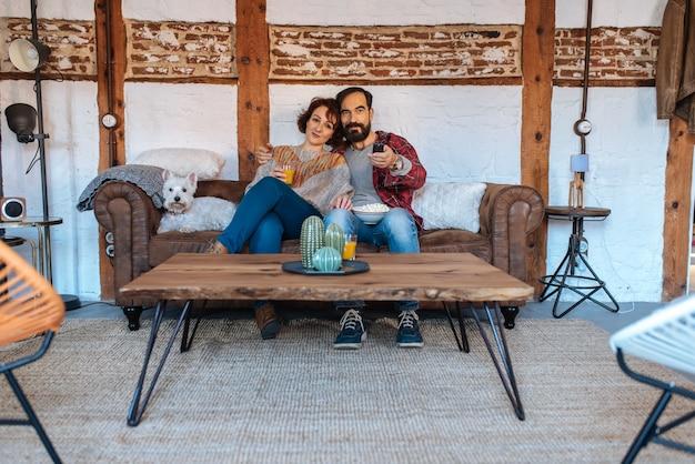 テレビを見て、ポップコーンを食べてソファで自宅でリラックスしたカップル