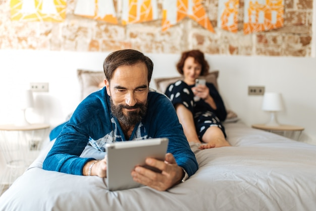 Couple relaxed at home in bed on the mobile phone and tablet