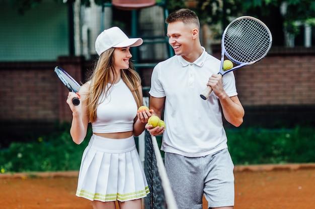여름에 밖에서 테니스 게임을 한 후 휴식을 취하는 커플.