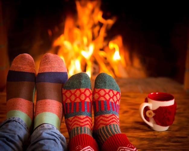 家でくつろぐカップル。暖炉のそばのクリスマスソックスの足。冬の休日のコンセプト