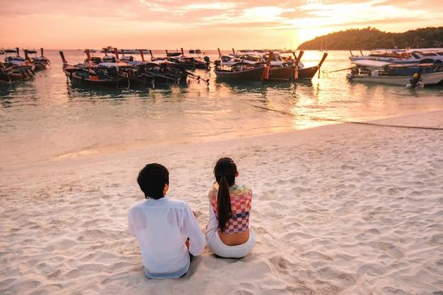 Couple relaxing beautiful sunset on koh lipe beach thailand