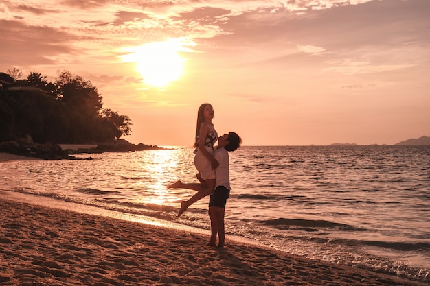 Couple relaxing beautiful sunset on koh lipe beach thailand