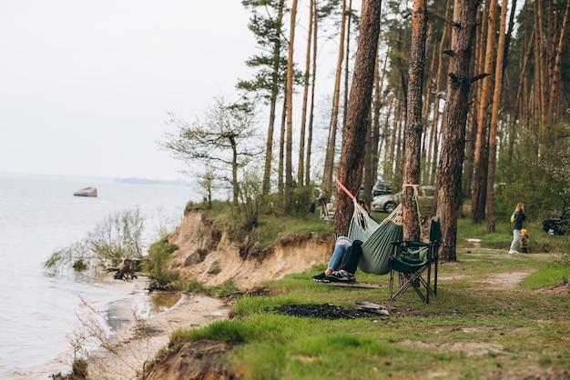 물이 내려다보이는 해먹에서 휴식을 취하는 커플