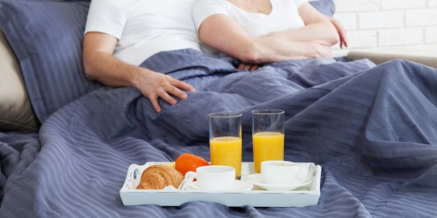 Пара расслабиться в постели с чашкой кофе