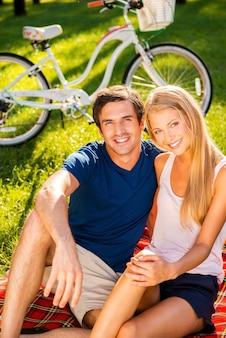 공원에서 휴식을 취하는 커플. 행복한 젊은 부부는 피크닉 담요에 앉아 자전거를 배경으로 공원에서 함께 휴식을 취합니다.