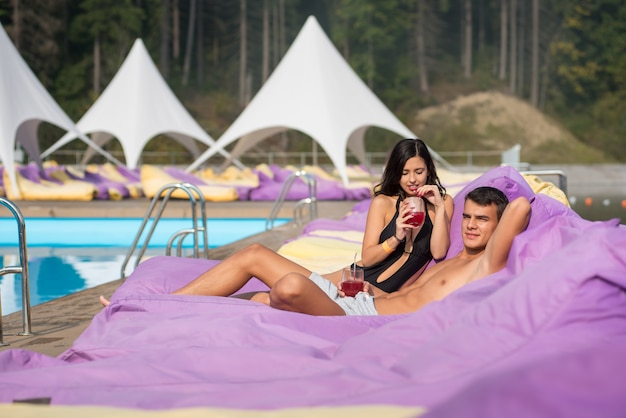 Couple relaxing near swimming pool