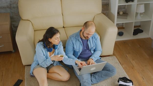 家具の後にインターネットでフロアブラウジングでリラックスしたカップル。