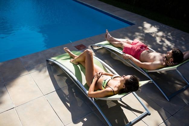 화창한 날에 수영장가에서 라운지 의자에 편안한 커플