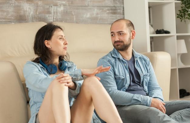 寄木細工の床でリラックスして会話をしているカップル