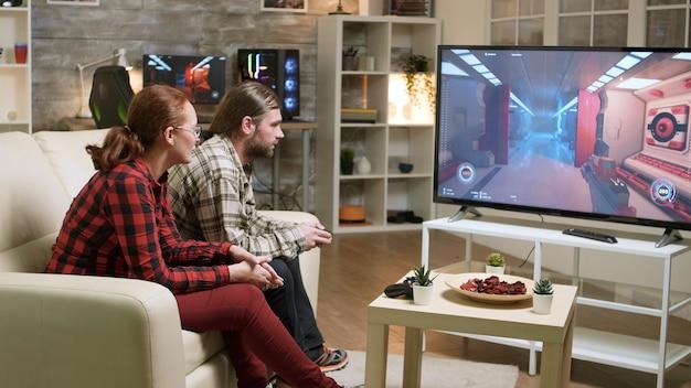 テレビでビデオゲームをして仕事で忙しい一日を過ごした後、ソファでリラックスしたカップル。