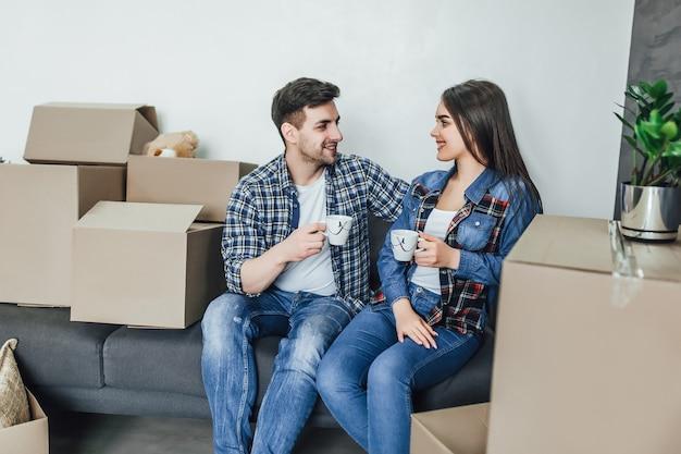新しい家で温かい飲み物とソファでリラックスしたカップル
