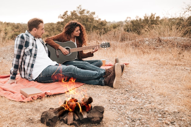 Couple relaxing outdoors next to a camp fire