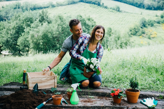 Couple relaxing and planting some flowers in their countryside house yard
