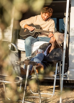 Couple relaxing and playing guitar next to car while on a road trip