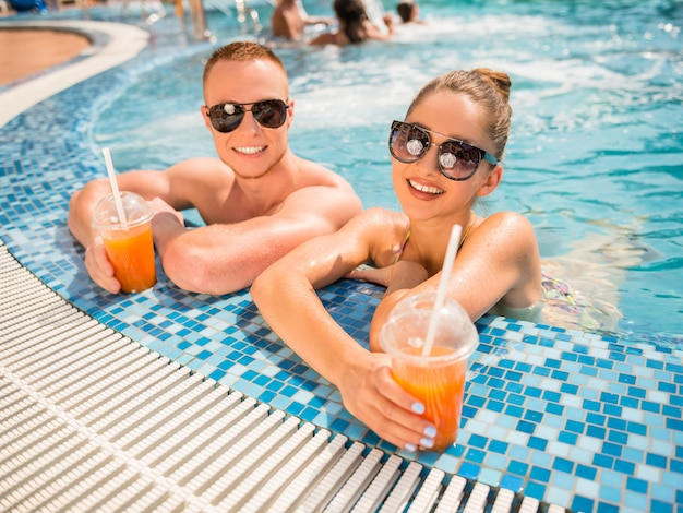 Couple relaxing in resort swimming pool, drinking cocktails.