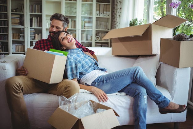 Couple relaxing on sofa while unpacking carton boxes