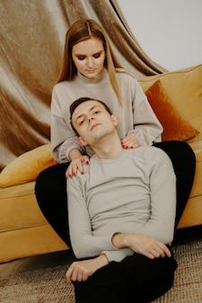 ソファで一緒にリラックスするカップル。ソファで楽しんで幸せな若いカップル。