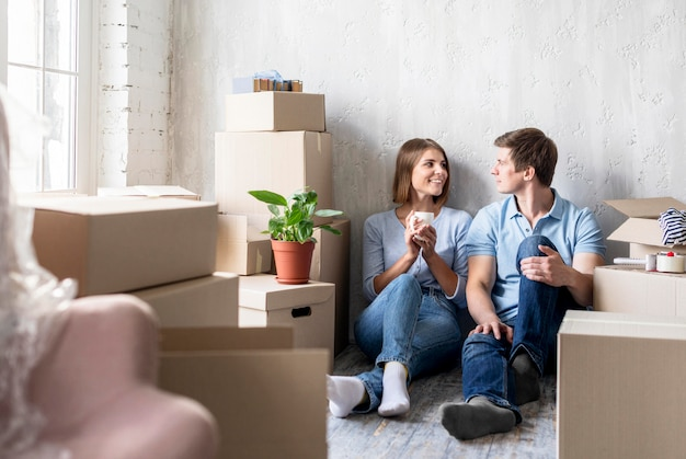 Couple relaxing while packing to move house