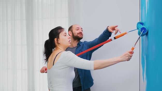 Пара перекрашивает стену квартиры синей краской с помощью валика. ремонт квартир и строительство дома одновременно с ремонтом и благоустройством. ремонт и отделка.