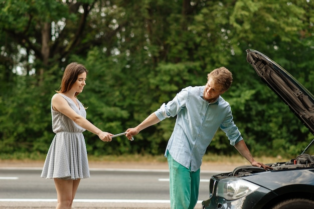 Пара ремонтирует авто на дороге, поломка автомобиля Premium Фотографии
