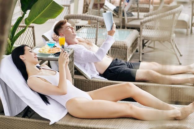 スイミングプールで休んでいるカップル