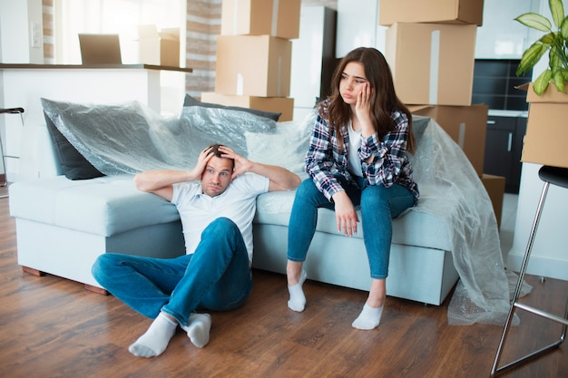 Couple resting on couch after moving in, man and woman relaxing on sofa just moved into the apartment with cardboard boxes on floor,.tired and upset homeowners and first day in new home