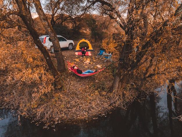湖のキャンプ場の近くで休んでいるカップル秋秋シーズン