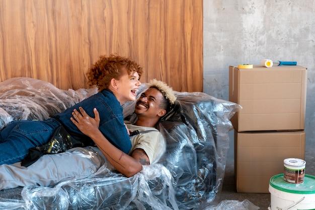 페인트 통 옆에 있는 새 집의 소파에서 휴식을 취하는 커플