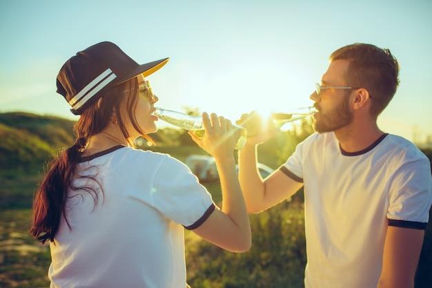 Пара отдыхает на пляже в летний день у реки. любовь, счастливая семья, отдых, путешествия, летняя концепция.