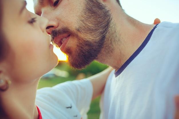川の近くの夏の日にビーチで休んでいるカップル。愛、幸せな家族、休暇、旅行、夏のコンセプト。