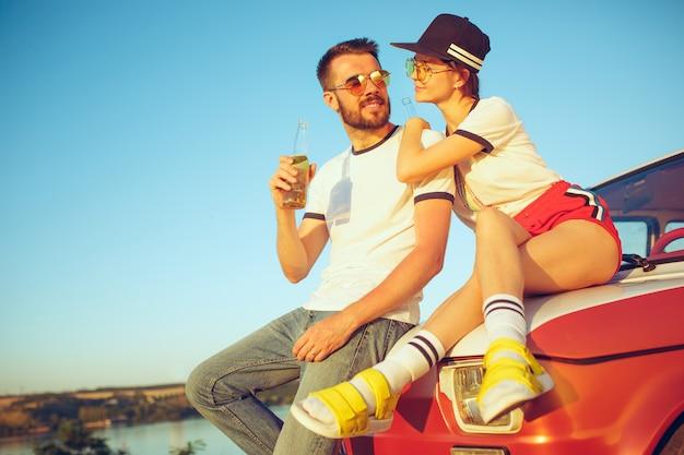 川の近くの夏の日にビーチで休んでいるカップル。愛、幸せな家族、休暇