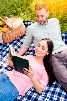 Couple resting on picnic in park