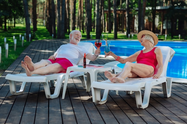 Couple of retired people feeling unbelievable while having rest lying on deck chair