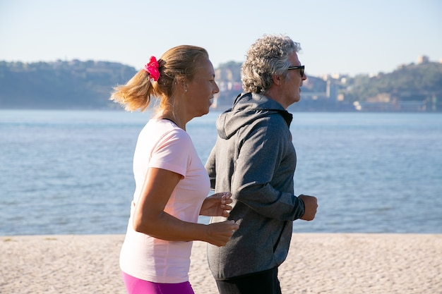 Couple of retired people wearing sports clothes, enjoying morning run, jogging along river bank in morning. side view. lifestyle and retirement concept