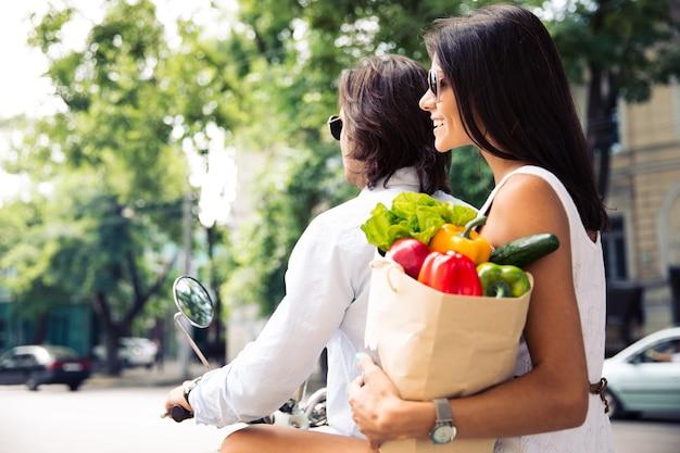 Пара, едущая на скутере в городе