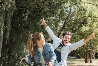 Couple riding bike in park