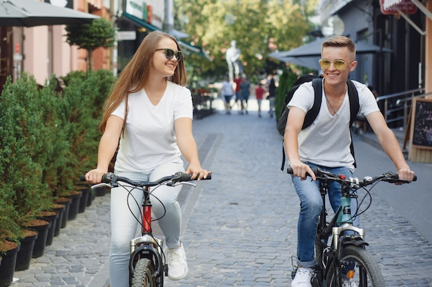 Couple riding bikes in summer city
