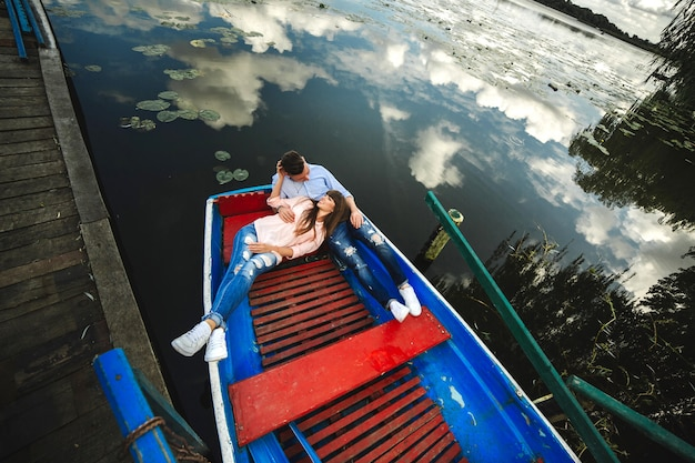 A couple riding a blue boat on a lake. romance. emotional couple.