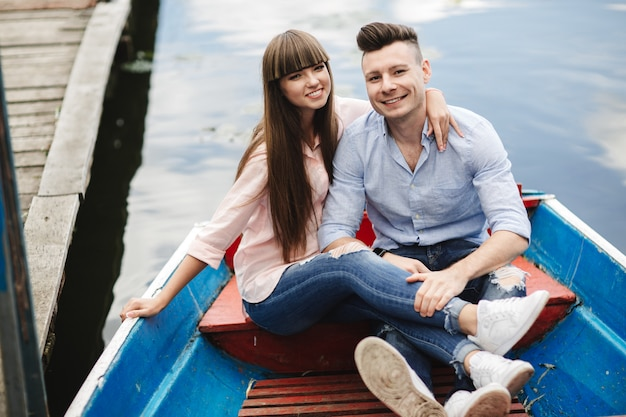 A couple riding a blue boat on a lake.