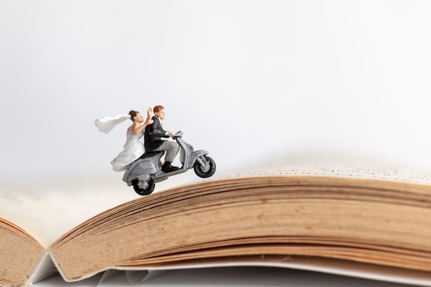 Couple riding the motorcycle on old book