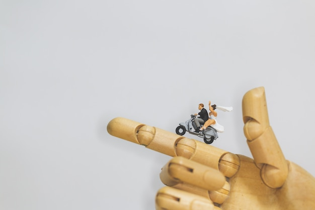 Couple riding the motorcycle on wooden hand with grey  background