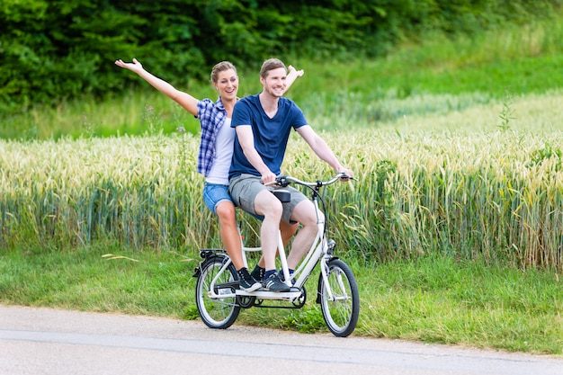 Couple riding tandem bike together in the country