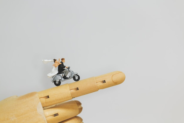 Пара езда на мотоцикле на деревянной руке с серым фоном