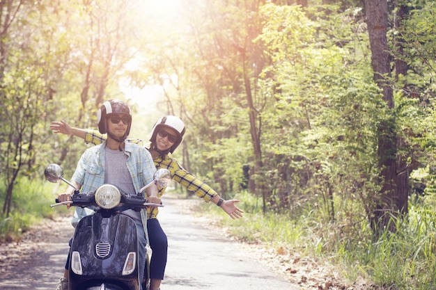 Couple riding their scooter through forest. life style idea concept