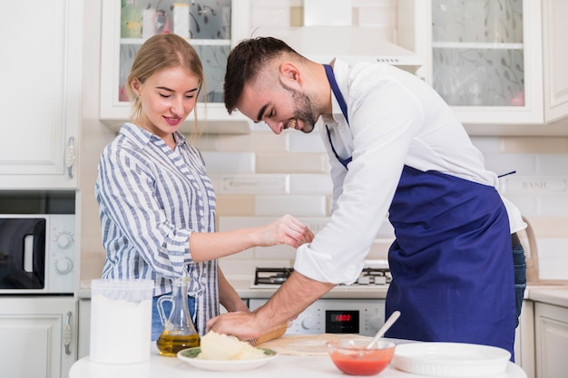 Couple rolling dough for pizza at table