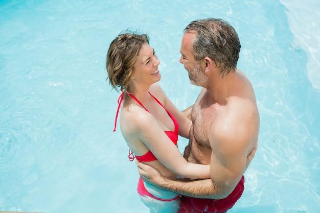 スイミングプールでロマンシングカップル