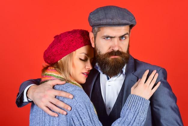 カップル。暖かい服を着たロマンチックなカップル。ガールフレンドを抱きしめるハンサムなひげを生やした男。愛の概念。流行りの服。ファッション服。秋冬ファッション。赤い背景で隔離。