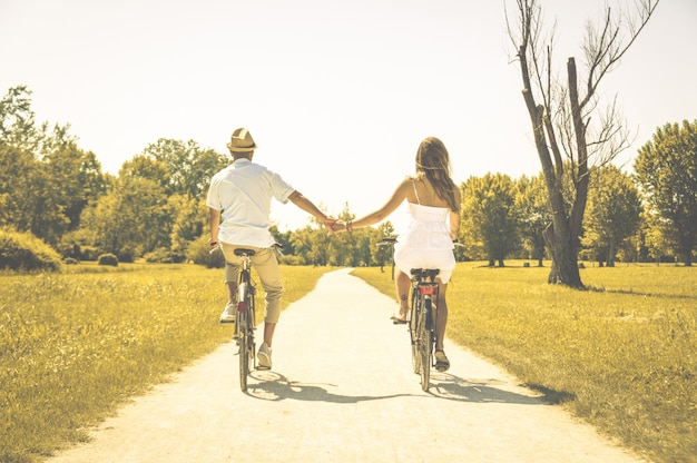 Couple of romantic lovers cycling - caucasian people - people, love, nature and lifestyle concept Premium Photo